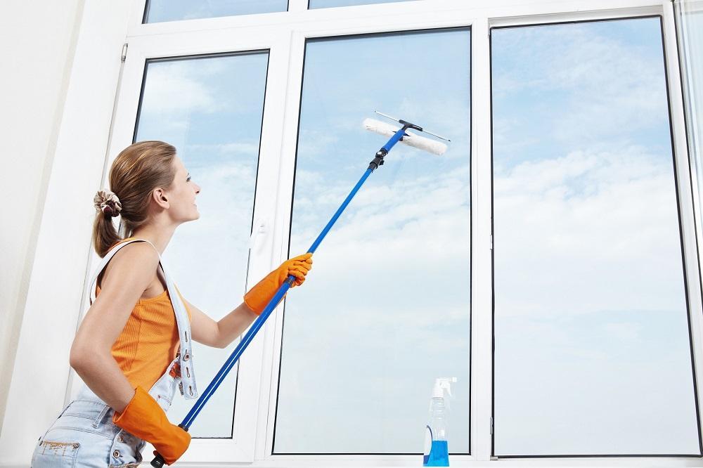 женщина моет окна шваброй